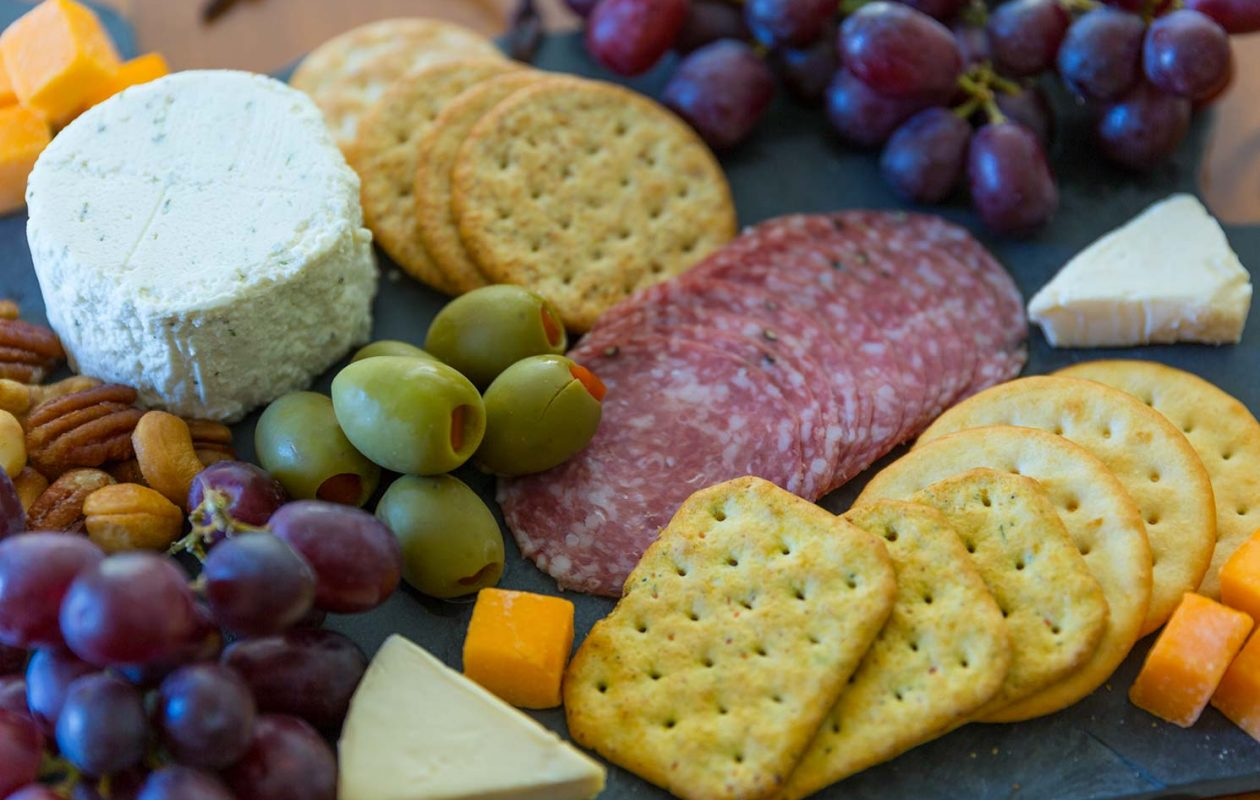 Assorted cheeses, crackers, fruit and olives