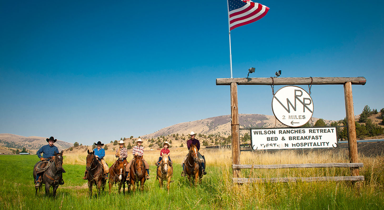 Wilson Family on horseback next to Wilson Ranches Retreat sign