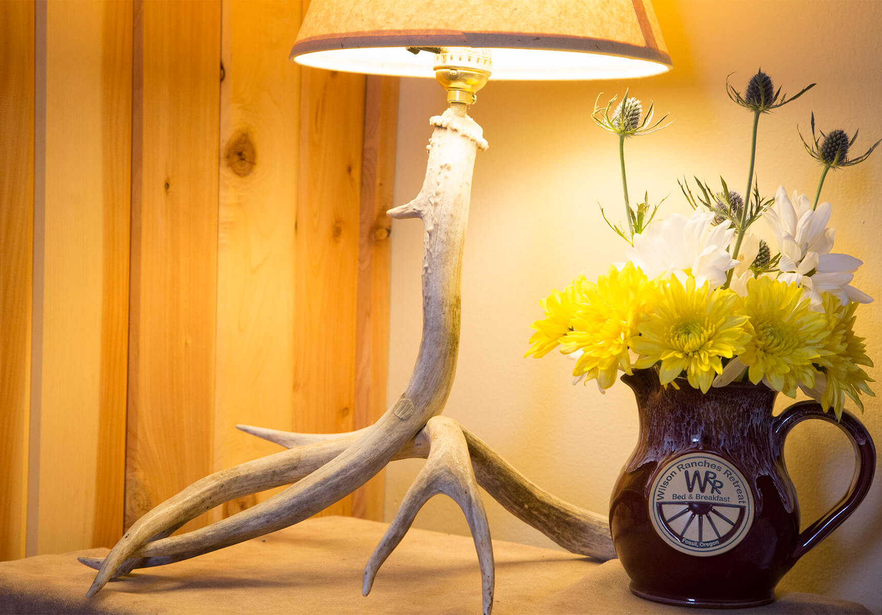 A antler lamp and vase with flowers on a end table