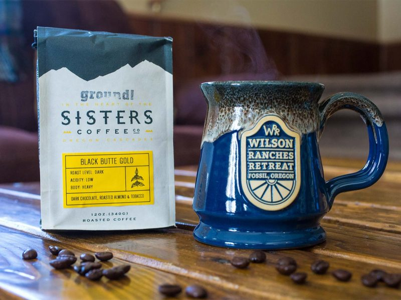 Blue and white Deneen Pottery mug with Wilson Ranches Retreat logo and a bag of Sisters Coffee