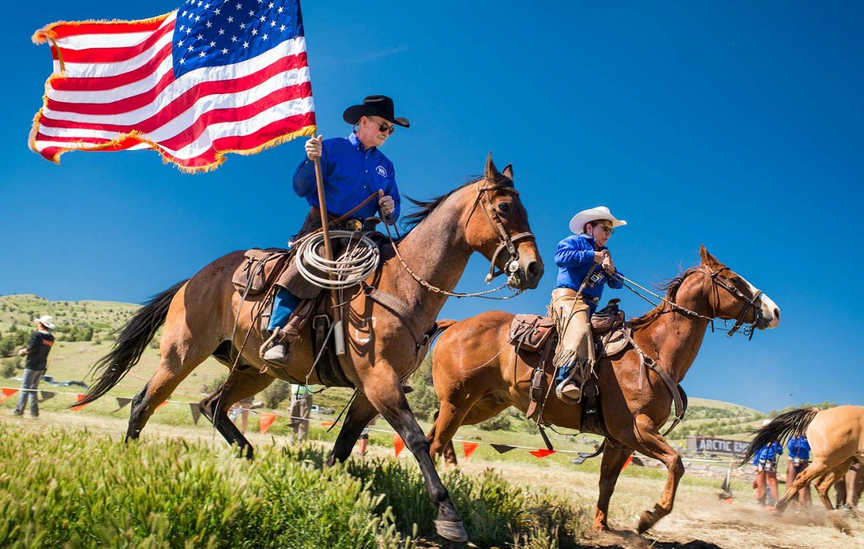 Two riders on horseback one holding an American Flag