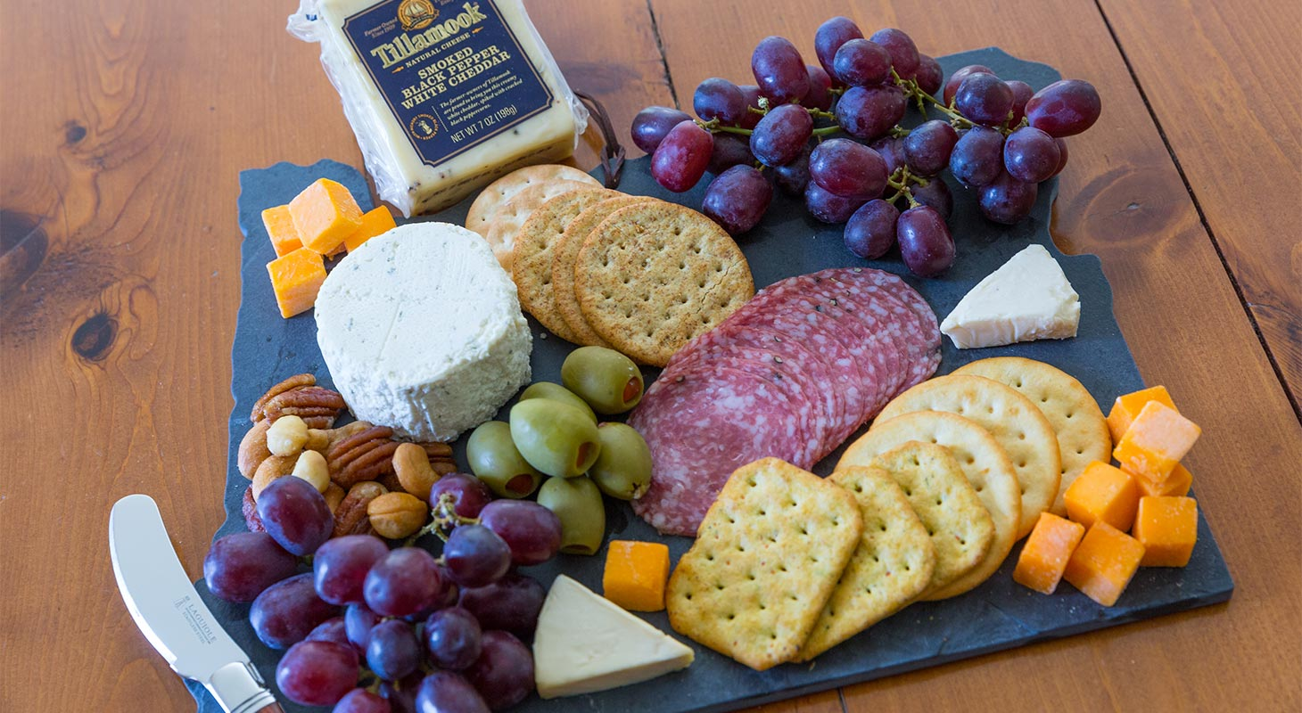 Assortment of cheese, crackers, fruit and nuts on a board