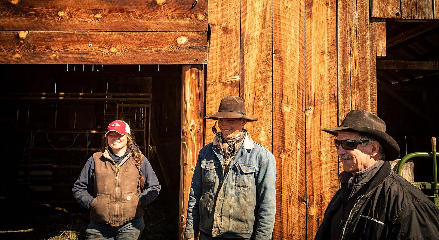 Three ranchers standing in front of a wooden barn