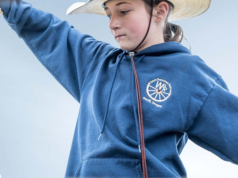 Girl in a cowboy hat wearing a sweatshirt with Wilson Ranches Retreat logo