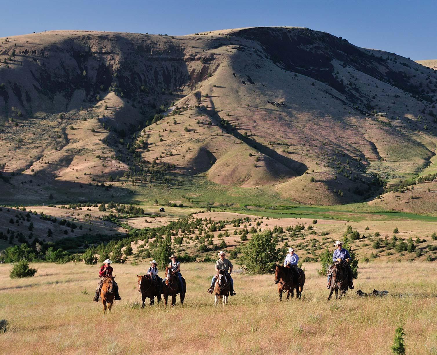 Group on horseback in front of scenic eastern oregon