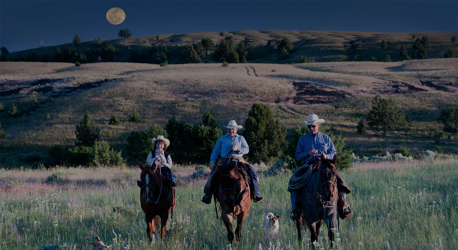 Three on horseback riding in a field with a rising full moon over a hill