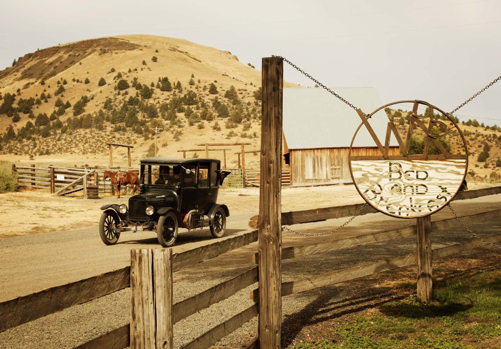 An old car near the sign to Wilson Ranches Retreat