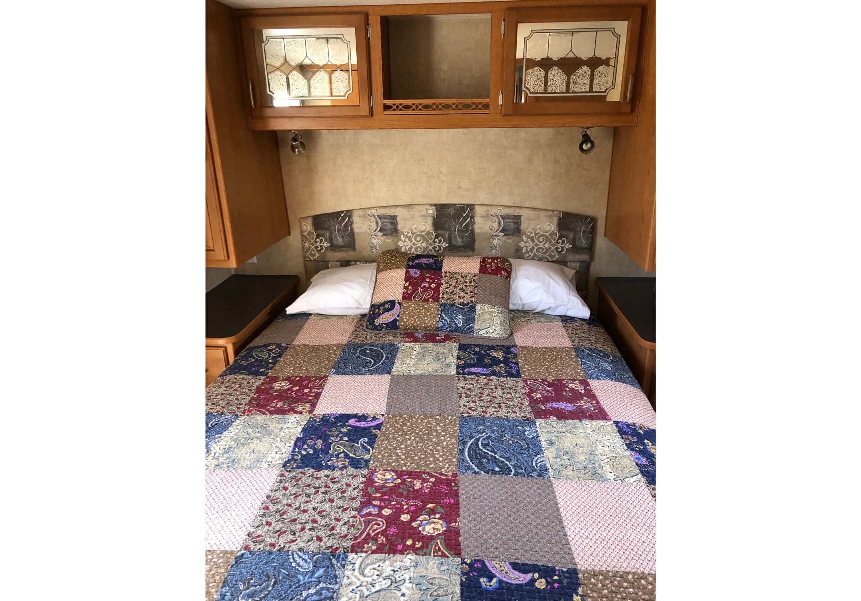 Queen bed with quilt and a cabinet with reading lamps